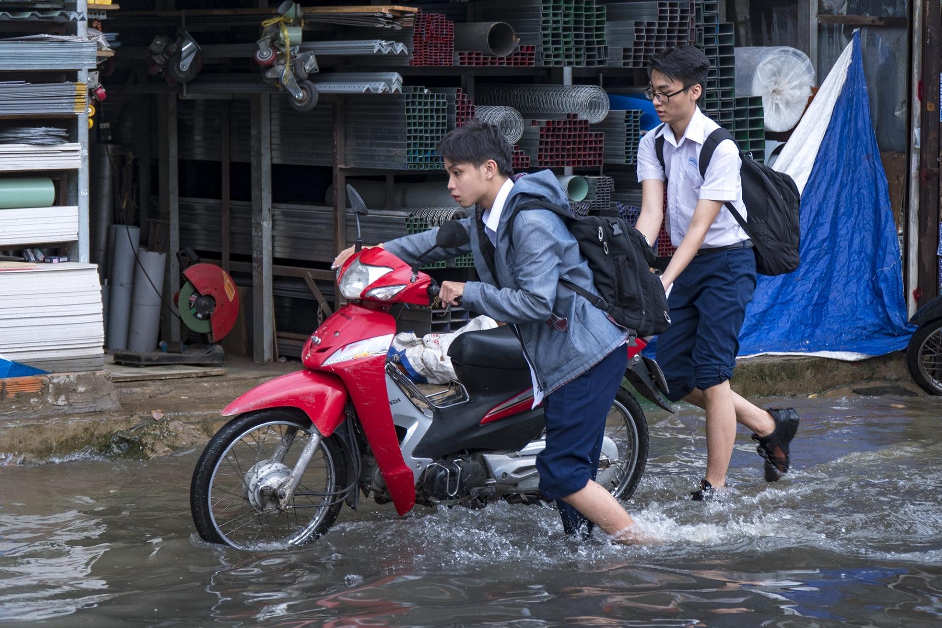 Người dân TP.HCM lội nước, đẩy xe chết máy sau cơn mưa giữa trưa
